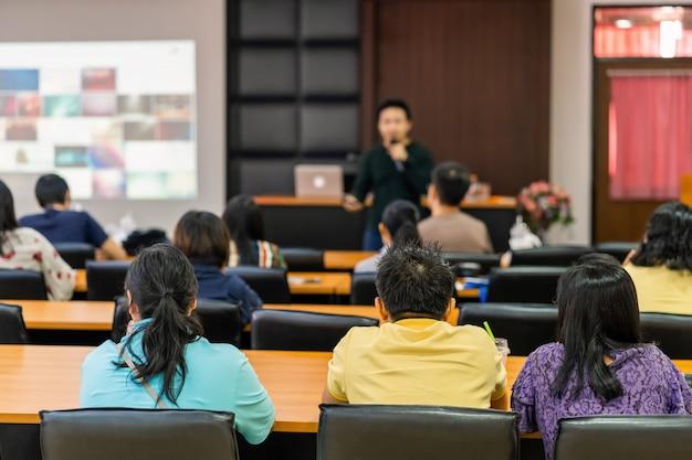 Hintere ansicht von hörenden sprechern des publikums auf dem stadium im konferenzsaal oder in der seminarsitzung, im geschäft und in der bildung über investitionskonzept