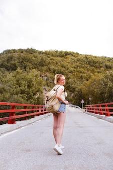 Hintere ansicht von jungen blondinen mit rucksack gehend auf die straße über einer brücke nahe dem berg. reise- und erlebniskonzept. reisender mitten in waldland. alleine reisen