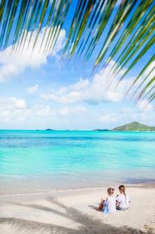 Hintere ansicht von kleinen mädchen auf sandigem strand. glückliche kinder sitzen unter der palme am tropischen strand