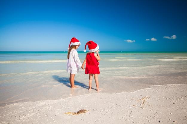 Hintere ansicht von kleinen netten mädchen in den weihnachtshüten auf dem exotischen strand