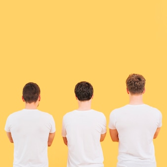Hintere ansicht von männer im weißen t-shirt, das gegen gelben hintergrund steht