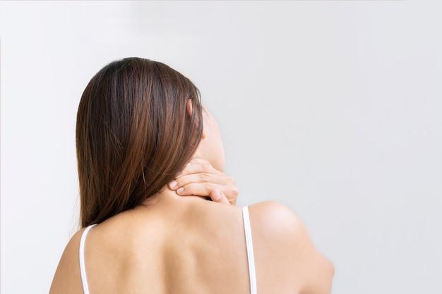 Hintere ansicht von oung asiatischer frau, die unter nackenschmerzen leidet, isoliert auf weißem hintergrundstudioschuss kopieren raumnahaufnahme