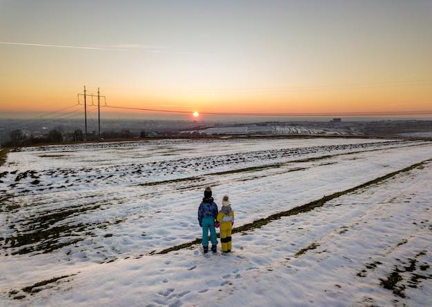 Hintere ansicht von zwei kleinkindern in der warmen kleidung, die im gefrorenen schneefeldhändchenhalten auf kopienraumhintergrund der untergehenden sonne und des klaren blauen himmels steht.