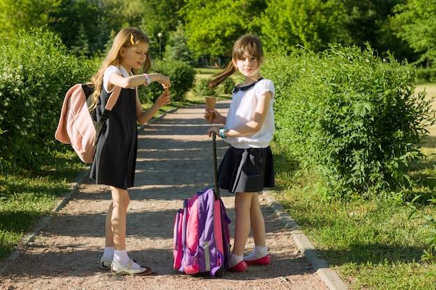 Hintere ansicht von zwei schulmädchenfreundinnen mit rucksäcken