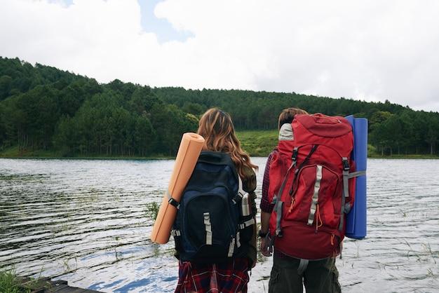 Hintere ansicht von zwei wanderern mit den rucksäcken, die wasser gegenüberstellen
