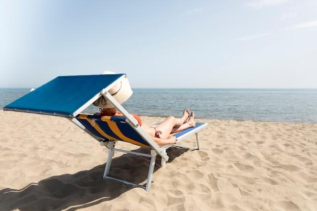 Hintere ansichtfrau auf dem ein sonnenbad nehmenden strandstuhl