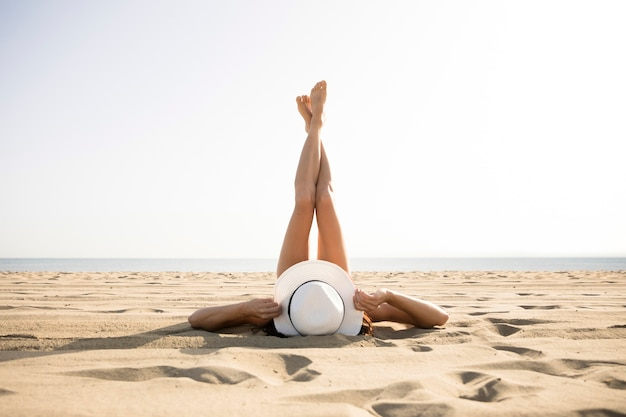 Hintere ansichtfrau auf strand mit den füßen oben