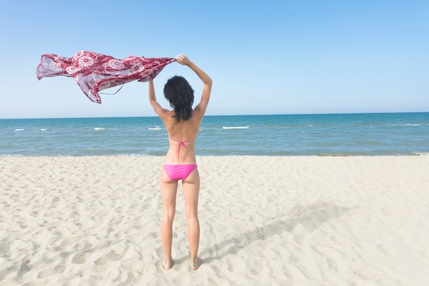 Hintere ansichtfrau, die auf dem strand betrachtet das meer steht