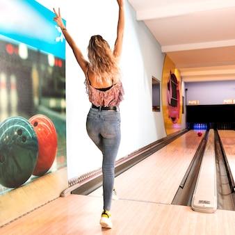 Hintere ansichtfrau, die bowlingspiel spielt