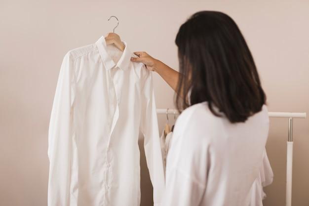 Hintere ansichtfrau, die ein weißes hemd betrachtet