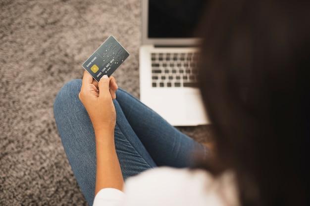 Hintere ansichtfrau, die eine kreditkarte auf boden hält