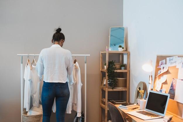 Hintere ansichtfrau, die in der garderobe schaut