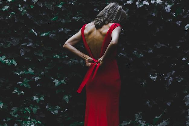 Hintere ansichtfrau, die kleid bindet