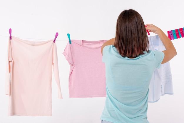 Hintere ansichtfrau, die kleidung auf wäscheleine vereinbart