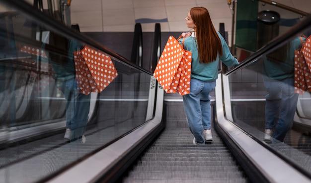 Hintere ansichtfrau, die papiertüte auf rolltreppe hält