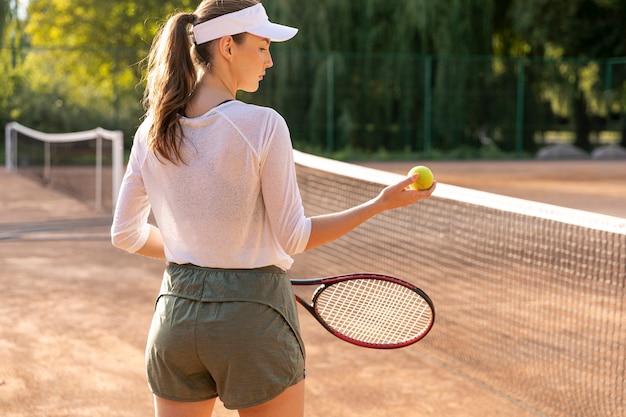 Hintere ansichtfrau, die tennis spielt