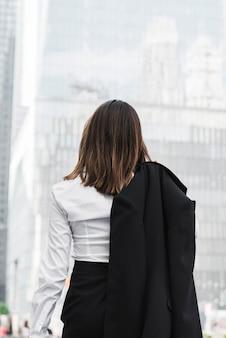 Hintere ansichtgeschäftsfrau, die eine jacke hält