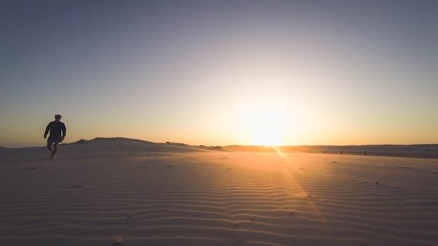 Hintere ansichtschattenbild eines läufermannes, der entlang auf den strand bei sonnenuntergang mit sonne im hintergrund läuft