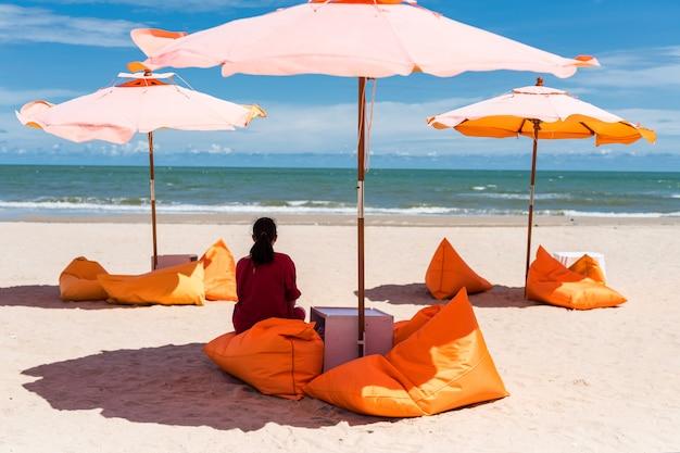 Hintere asiatische frau sitzen auf sitzsack sitz unter orange sonnenschirm, um tropisches meer und strand im sommer in cha-am, petchburi, thailand zu sehen. mädchen entspannen im urlaub auf der insel.