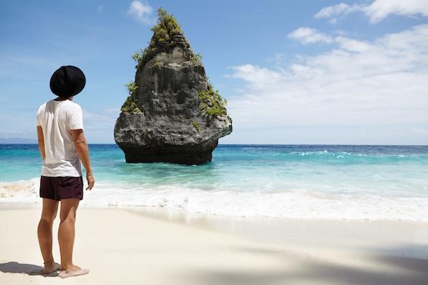 Hintere aufnahme des stilvollen jungen mannes mit nackten füßen, die allein auf sandstrand stehen und erstaunliche felseninsel im ozean betrachten, während ferien in den tropen verbringen. menschen-, reise- und abenteuerkonzept