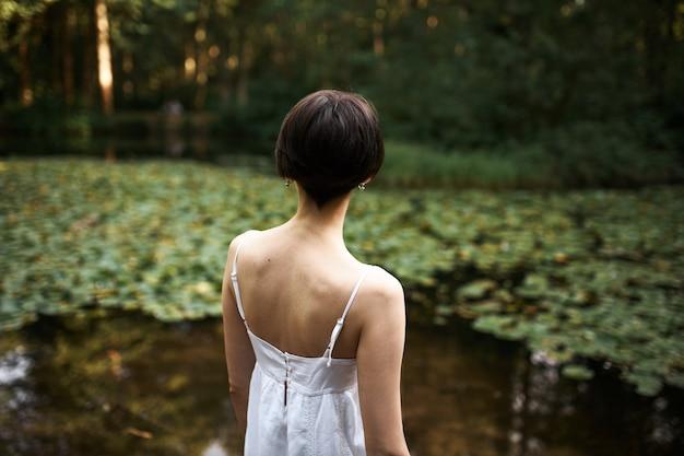 Hintere aufnahme einer nicht wiedererkennbaren kurzhaarigen jungen frau in einem weißen kleid mit riemen, das sich am teich im park entspannt und die wunderschöne landschaft und den heißen sommertag genießt. rückansicht der frau, die allein im freien geht