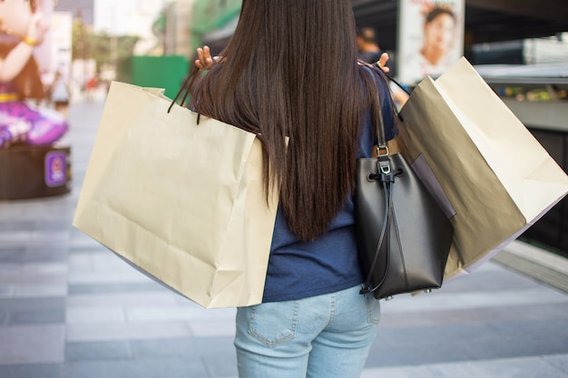 Hintere frau mit papiereinkaufstasche. weicher fokus.