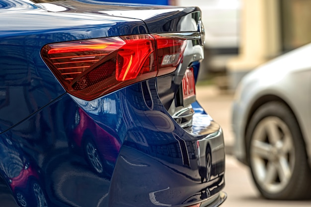 Hintere hälfte mit rücklichtern eines geparkten autos am straßenrand, fahrzeugaußendetails, nahaufnahme