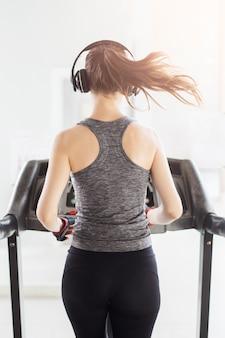 Hintere sportfrau, die auf tretmühle in der turnhalle, gesunder lebensstil rüttelt