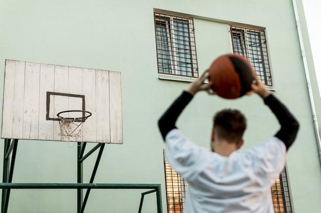 Hinterer ansichtmann, der einen basketball wirft