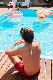 Hinterer ansichtmann, der entlang des pools anstarrt