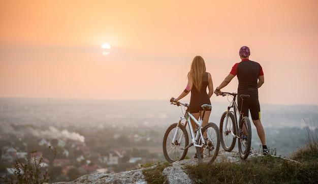Hinterer ansichtmann und -frau mit den sportfahrrädern, die auf die oberseite eines hügels den sonnenuntergang genießend stehen
