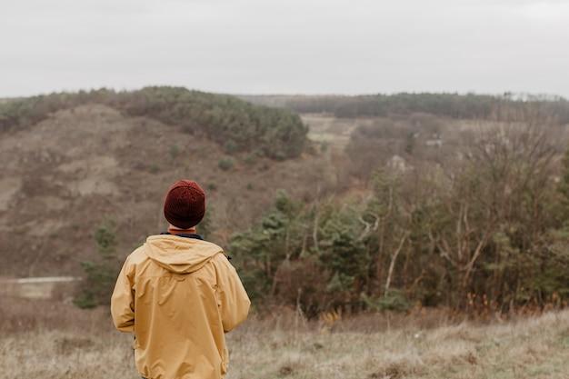 Hinterer ansichtreisender, der landschaft betrachtet