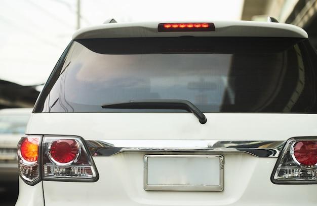 Hinterer aspekt oder hintere ansicht des suv-autos in der realen straße der tageszeit