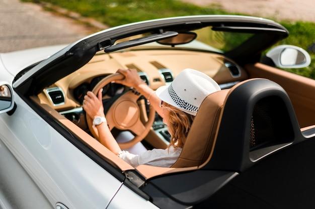 Hinterer schuss der stilvollen frau im auto