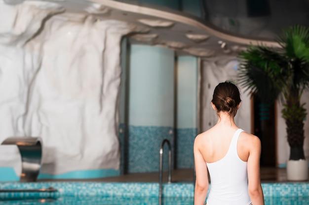 Hinteres ansichtmädchen, das in badeanzug aufwirft
