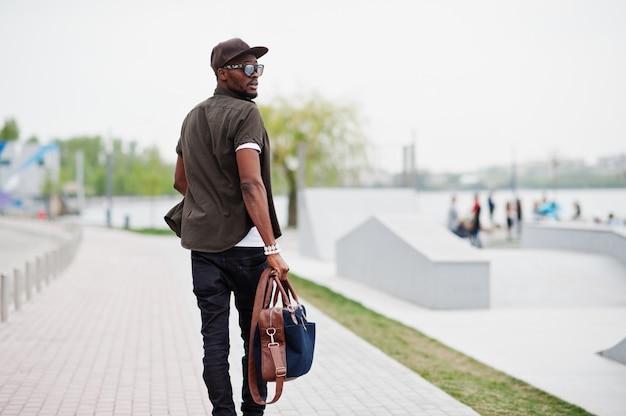 Hinteres ansichtporträt der gehenden stilvollen afroamerikanermannabnutzung auf sonnenbrille und kappe mit der handtasche im freien. street fashion schwarzer mann.