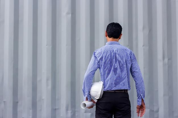 Hinteres ansichtporträt des asiatischen ingenieurs pläne gegen wand bei der stellung halten auf baustelle, kopienraum