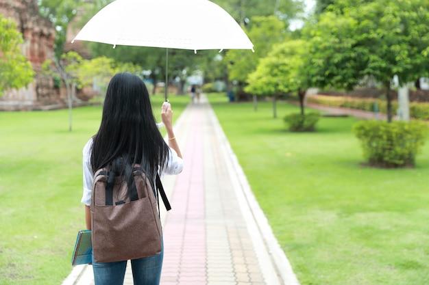 Hinteres ansichtporträt des schönen asiatischen reisenden, der regenschirm im alten tempel mit rucksack und karte hält