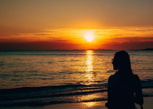 Hinteres ansichtporträt einer einsamen frau mit sonnenbrille am strandsonnenuntergang.