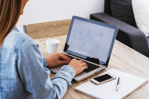 Hinteres ansichtporträt einer zufälligen geschäftsfrau, die an laptop im büro arbeitet