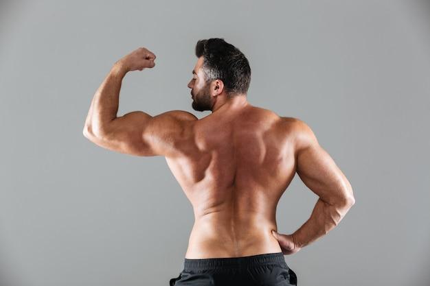 Hinteres ansichtporträt eines muskulösen hemdlosen männlichen bodybuilders