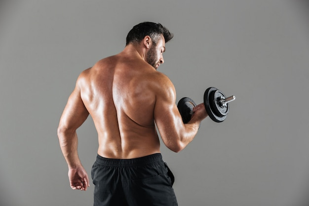 Hinteres ansichtporträt eines muskulösen starken hemdlosen männlichen bodybuilders