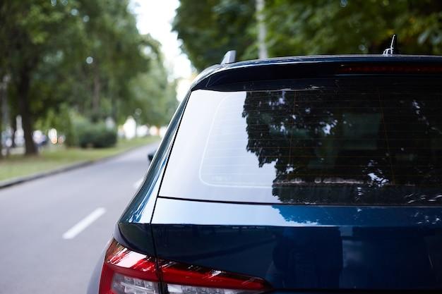Hinteres fenster des blauen autos geparkt auf der straße im sonnigen sommertag, rückansicht. modell für aufkleber oder abziehbilder
