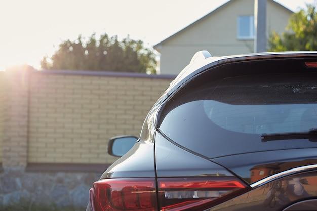 Hinteres fenster des grauen autos geparkt auf der straße im sonnigen sommertag, rückansicht. modell für aufkleber oder abziehbilder