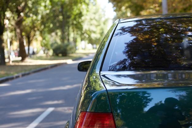 Hinteres fenster des grünen autos, das auf der straße geparkt wird.