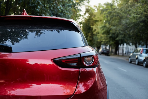 Hinteres fenster des roten autos geparkt auf der straße im sonnigen sommertag, rückansicht. modell für aufkleber oder abziehbilder
