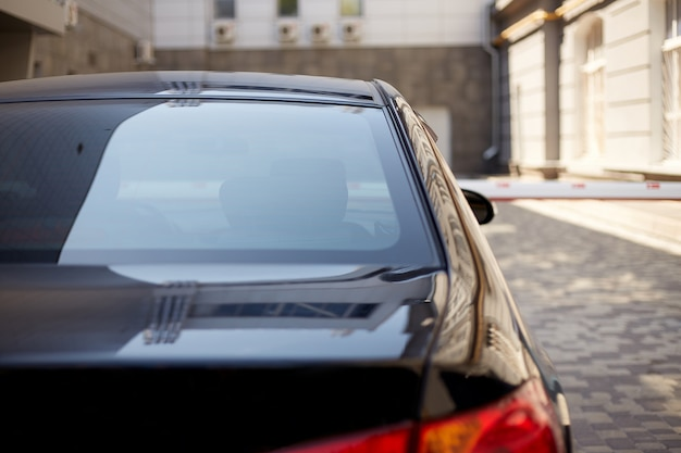 Hinteres fenster des schwarzen autos geparkt auf der straße im sonnigen sommertag, rückansicht. modell für aufkleber oder abziehbilder