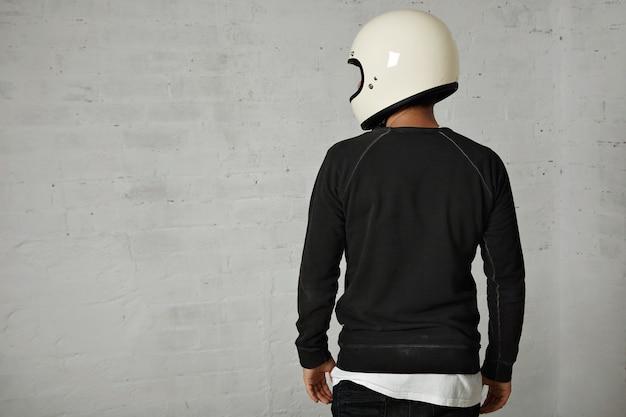 Hinteres porträt eines jungen mannes gekleidet in schwarzweiss-freizeitkleidung, die einen glänzenden weißen leeren motorradhelm trägt, der auf weiß lokalisiert wird