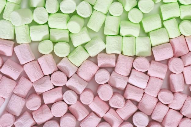 Hintergrund aus buntem zephyr grüne und rosa kleine süßigkeiten marshmallow