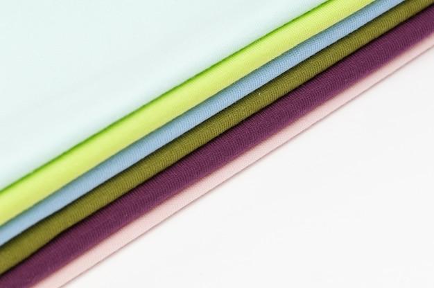 Hintergrund aus bunten stoffen und textilien, die aufeinander gestapelt sind